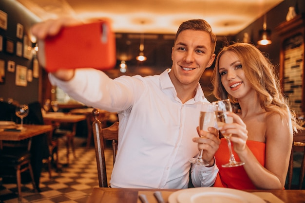 Couple drinking champaigne at a restaurant on valentines day Free Photo