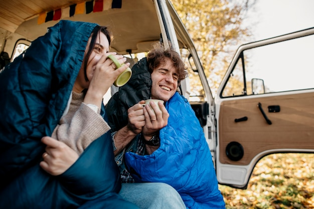 Couple drinking coffee from their van Free Photo