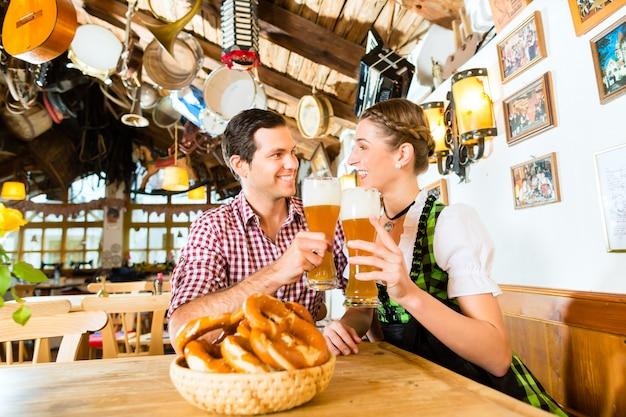 バイエルンレストランで小麦ビールを飲むカップル Premium写真