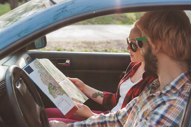 Couple driving and looking at map Free Photo