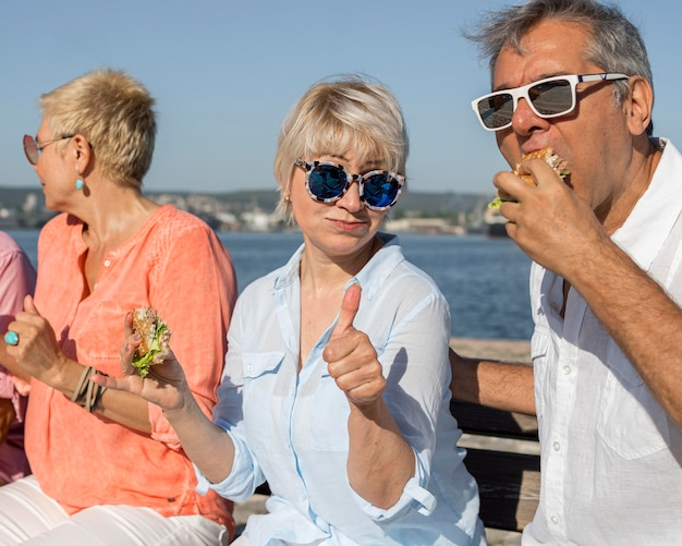 Couple eating burger outdoors and giving thumbs up Free Photo