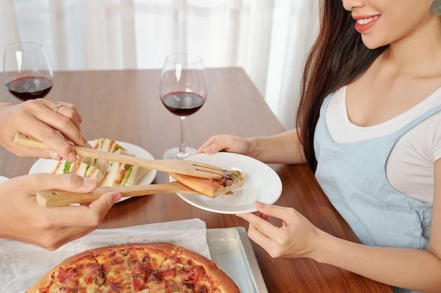 Пара, едящая пиццу дома Premium Фотографии