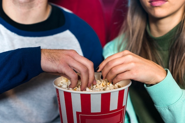 Couple eating popcorn in cinema Free Photo