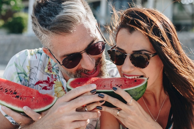 Couple eating watermelon at the beach Premium Photo