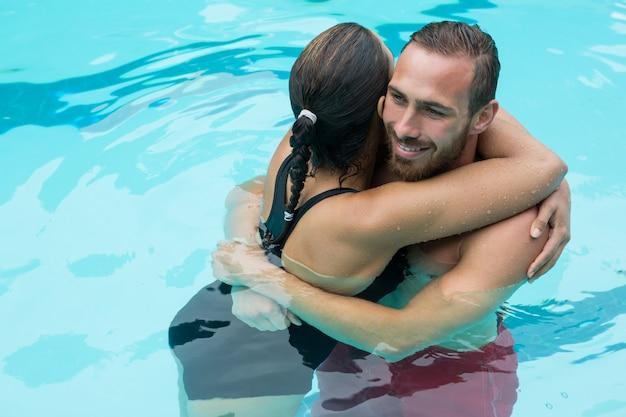 スイミングプールを受け入れるカップル Premium写真