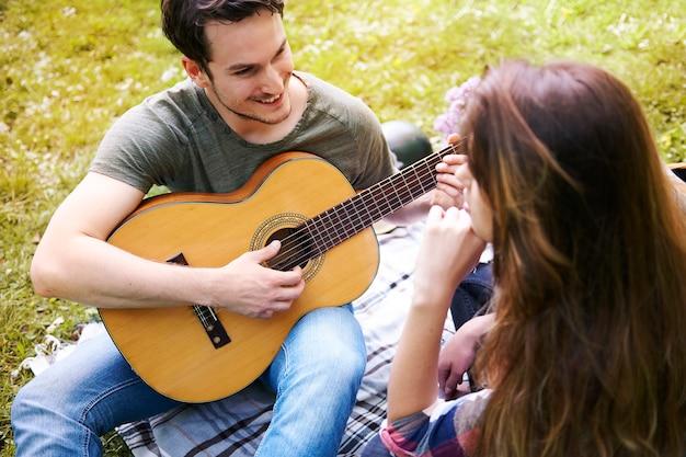 공원에서 피크닉을 즐기는 커플. 기타를 연주하는 남자. 로맨틱 데이트 무료 사진