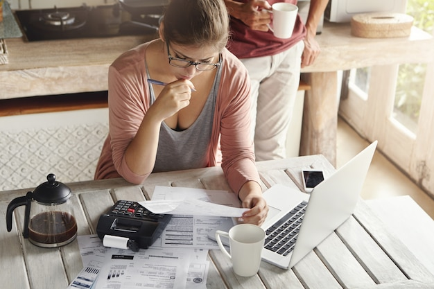 Couple facing debt problems, not able to pay out their mortgage. thoughtful woman looking frustrated, holding pen while managing family budget, making calculations using calculator and notebook pc Free Photo