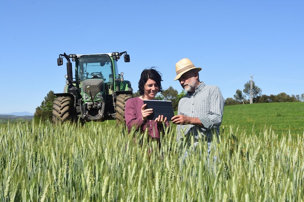 Couple of farmers in a field with a digital tablet Premium Photo