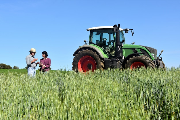 Couple of farmers in a wheat field with a tractor Premium Photo