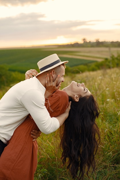 Couple in a field. woman in a brown dress. Free Photo