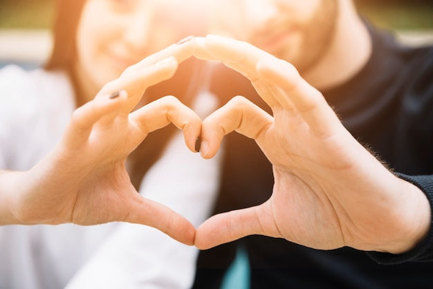 Couple forming heart with hands Free Photo