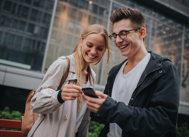 Couple or friends laughing funny and having fun with a smart phone in a big city street Premium Photo