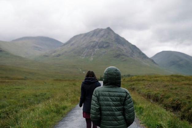 Couple of friends walking through the rain in glen etive, scotland Free Photo