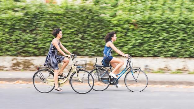 A couple of friends with bikes, motion blur. Premium Photo