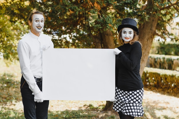 Couple funny mimes holding sign Premium Photo