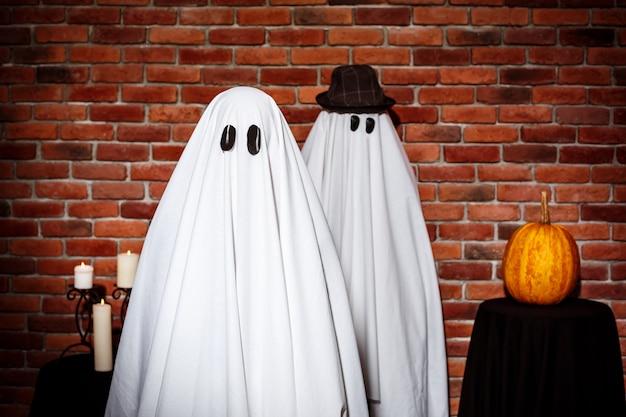 Coppia di fantasmi in posa sul muro di mattoni. festa di halloween. Foto Gratuite