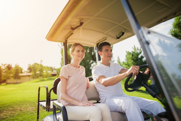 Couple in a golf cart people going to play golf. Premium Photo