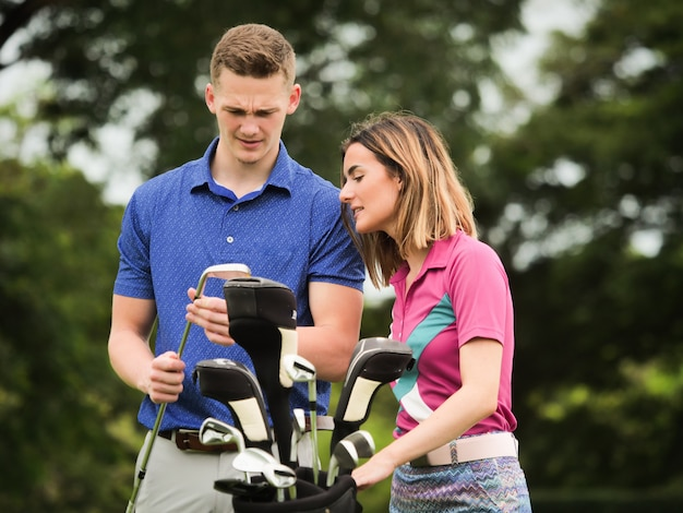 Couple golf concept : young man teaching his girl friend playing golf Premium Photo