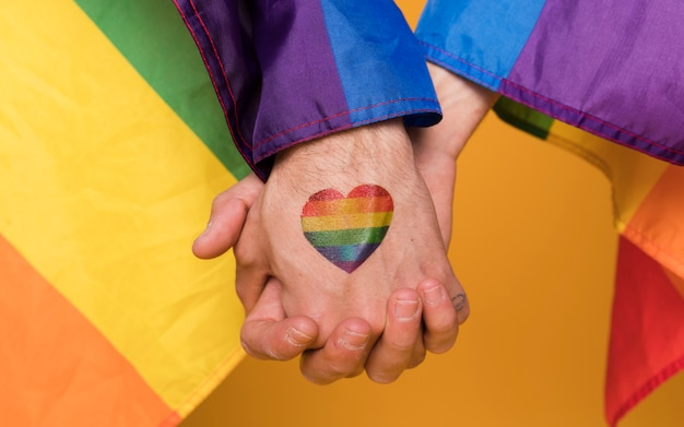 Couple of hands of homosexual men with rainbow heart image Free Photo