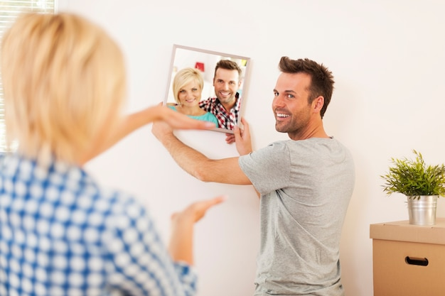 Couple hanging photo with frame on wall in new home Free Photo