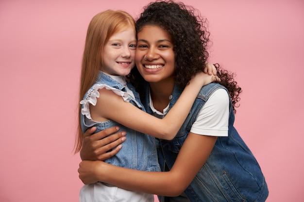 Coppia di giovani donne adorabili felici in gilet di jeans e camicie bianche che si abbracciano amorevolmente e guardando allegramente con sorrisi affascinanti, in posa contro il rosa Foto Gratuite