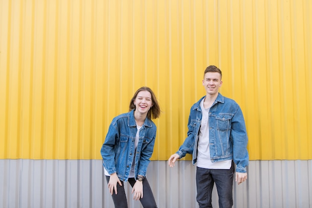 Couple of happy young people on background of yellow wall. smiling girl and man on yellow background. Premium Photo