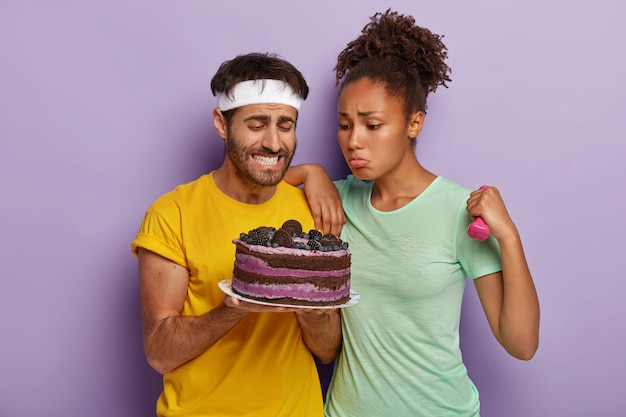 Couple have look at tasty sweet fruit cake, being hungry after exhausting training, woman holds dumbbell, dressed in casual clothes Free Photo