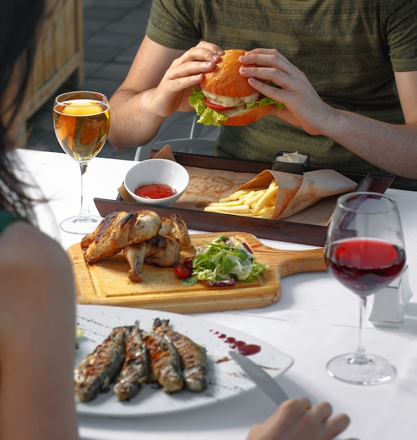 Couple having dinner with burger, fish and white,red wine. Free Photo