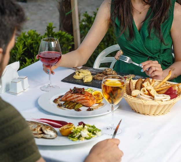 Couple having dinner with smoked salmon fillet, grilled fish,lamb steak and wine Free Photo