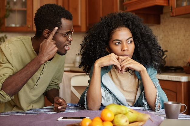 Couple having dispute. annoyed beautiful dark-skinned female sitting at kitchen table, ignoring screams and insults from her mad furious husband who is shouting at her, holding finger at his temple Free Photo