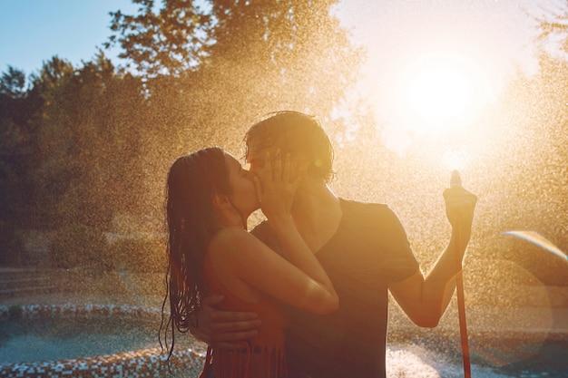 Le coppie che si divertono si versano con il tubo flessibile di giardino Foto Gratuite