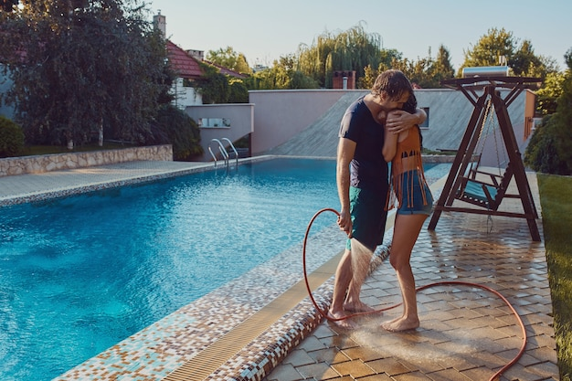 Couple having fun pour each other with garden hose Free Photo