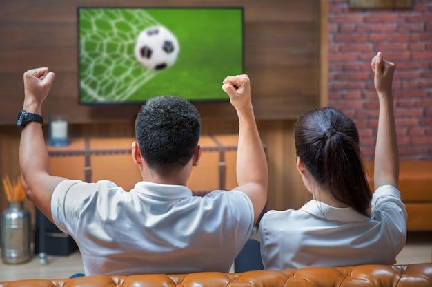 Пара весело смотрит футбол Premium Фотографии