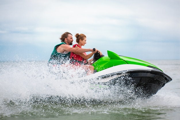 Couple having fun on water scooter summer sea activity Free Photo