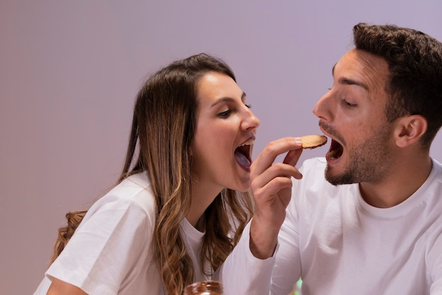 Couple having fun with biscuits Free Photo