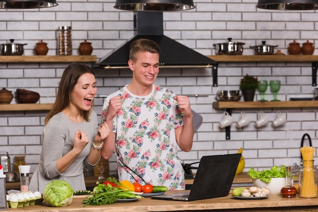 Couple having fun with laptop in kitchen Free Photo