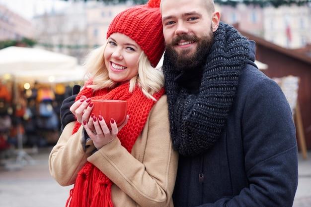 屋外でホットコーヒーを飲んでいるカップル 無料写真