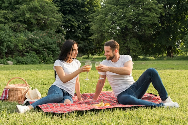 Couple having orange juice on picnic blanket Free Photo