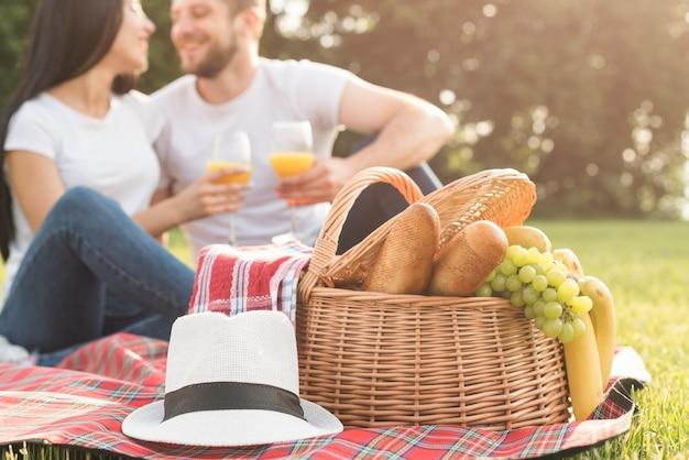 Couple having orange juice on picnic blanket Free Photo
