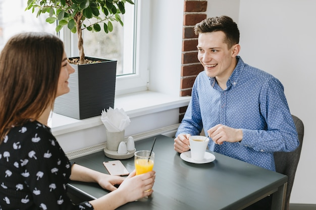 Couple having an orange juice in a restaurant Free Photo