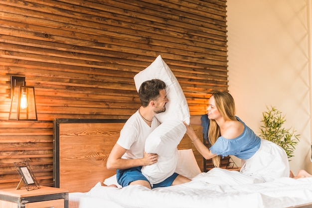 Couple having pillow fight on bed Free Photo