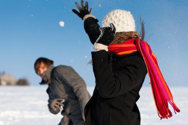 Couple having a snowball fight in winter Premium Photo