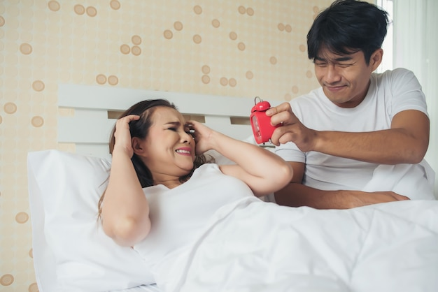 Couple having trouble with getting up early in the morning on the bed Free Photo