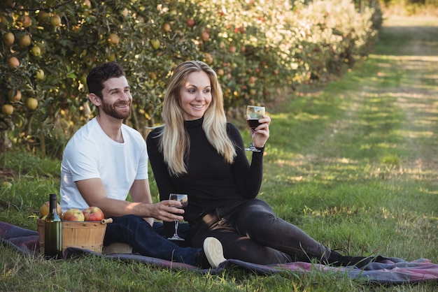 Couple having wine in apple orchard Free Photo