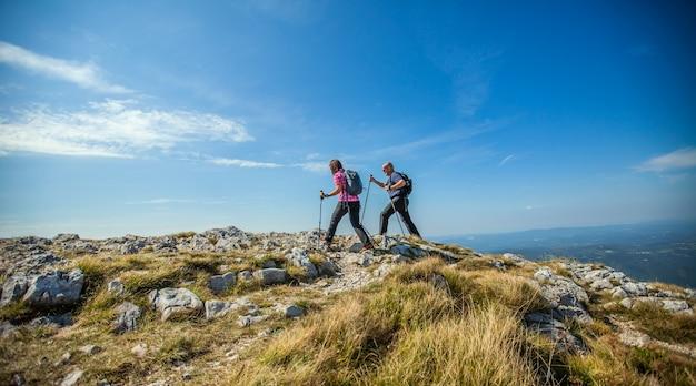 青い空を背景にスロベニアのナノス高原でハイキングするカップル 無料写真