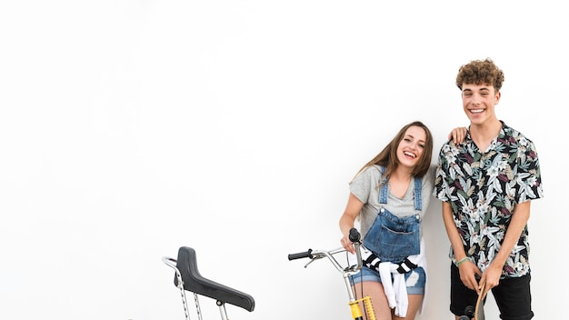 Couple holding bicycle and skateboard against white background Free Photo