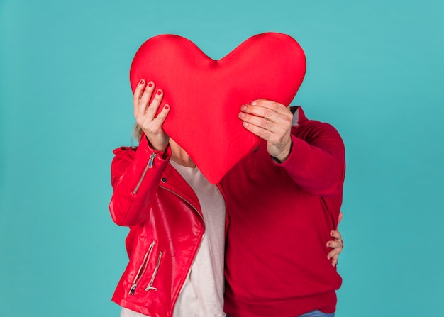 Couple holding big red heart Free Photo