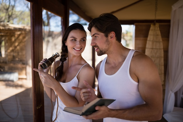 Couple holding binoculars while reading novel during safari vacation Free Photo