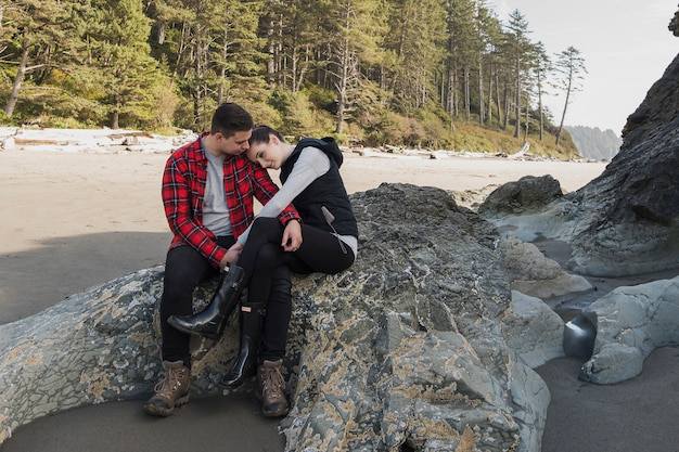 Couple holding each other at the beach on rock Free Photo