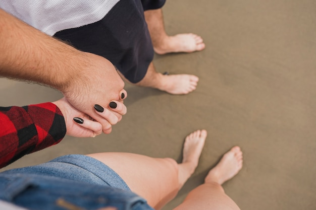 Couple holding hands on beach with bare feet Free Photo